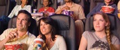 Moviegoers enjoying popcorn and soda in luxury movie theater seats