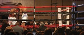 Indoor boxking ring with onlooking crowd