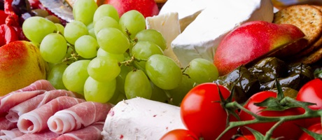 Catered food, grapes, tomatoes proscuitto and cheese with crackers