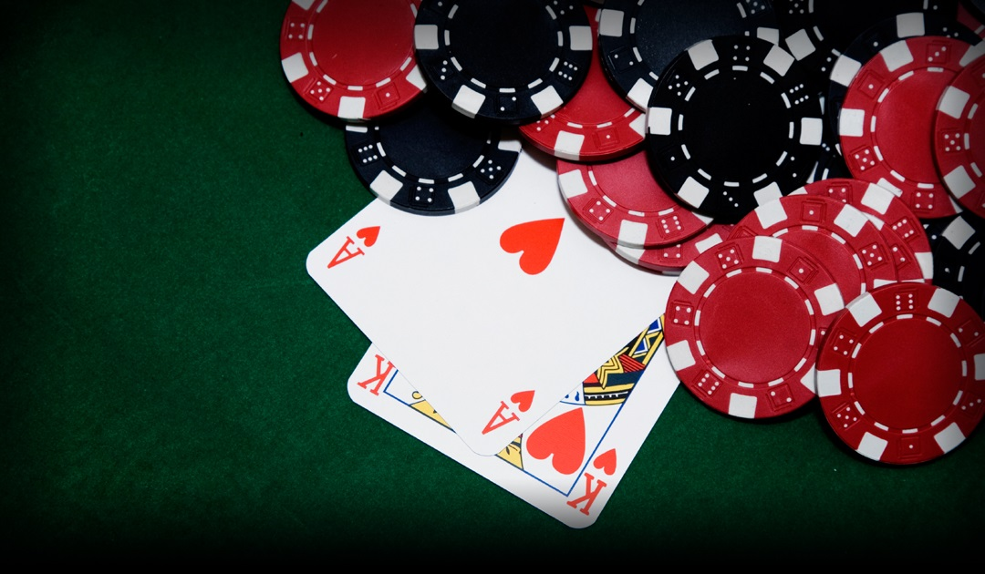 Ace and King of Hearts on green felt table with black and red chips