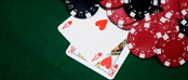 Ace and King of hearts cards on green felt with black and red chips