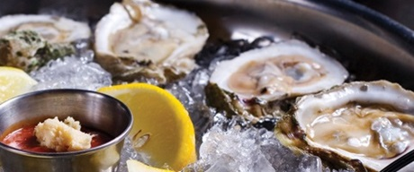 Oysters on ice with cocktail sauce and lemon slices