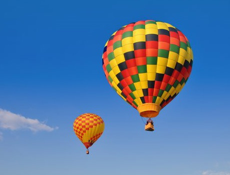 Two hot air balloons float into the sky